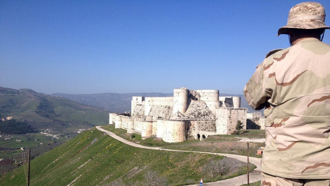 A government soldier looks out over the renowned Crusader castle Krak des Chevaliers near the Syria-Lebanon border after forces loyal to Syria's President Bashar al-Assad seized the fortress on March 20, 2014. (AFP)