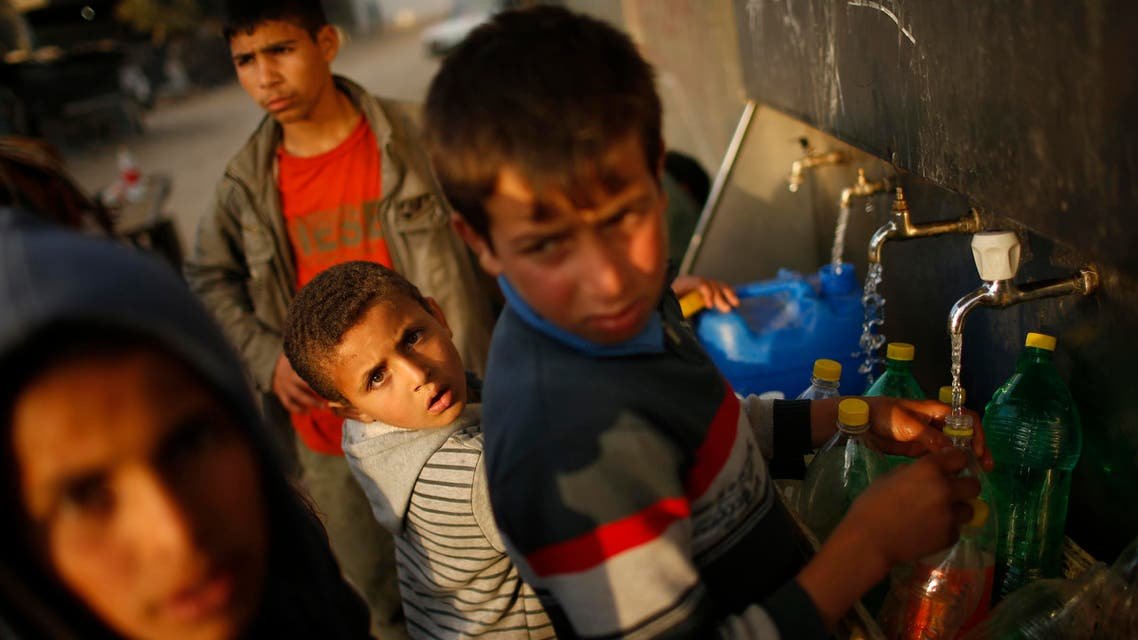 Palestinians fill containers with water from public taps in Beit Lahiya, near the border between Israel and the northern Gaza Strip. Reuters