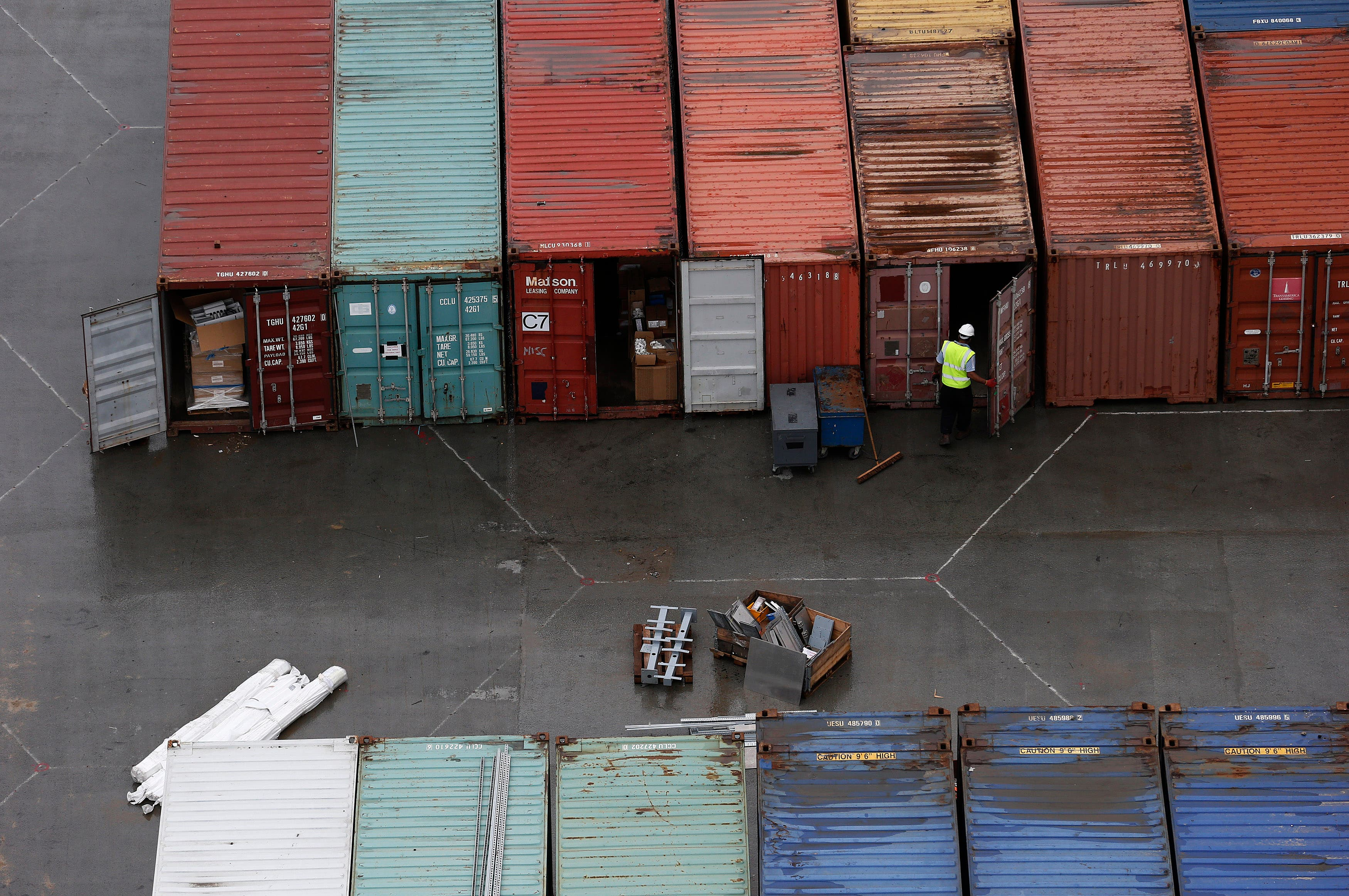 A worker opens the door of a container at DP World London Gateway container port in July, 2013. (File photo: Reuters)