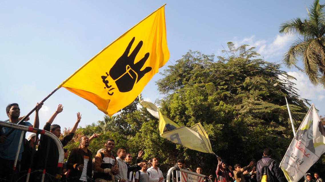 supporters of the Muslim Brotherhood and ousted Egyptian President Mohammad Mursi, wave a flag bearing the 'Rabaa' sign during a protest in front of at the main gate of the university in Cairo, Dec 9, 2013. (Reuters)