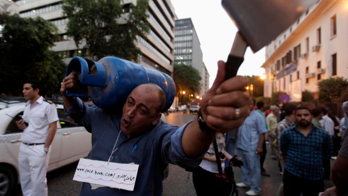 A man carries a gas cylinder and a cooking pot during a protest against high prices and the scarcity of gas, in Cairo September 27, 2012. (Reuters)