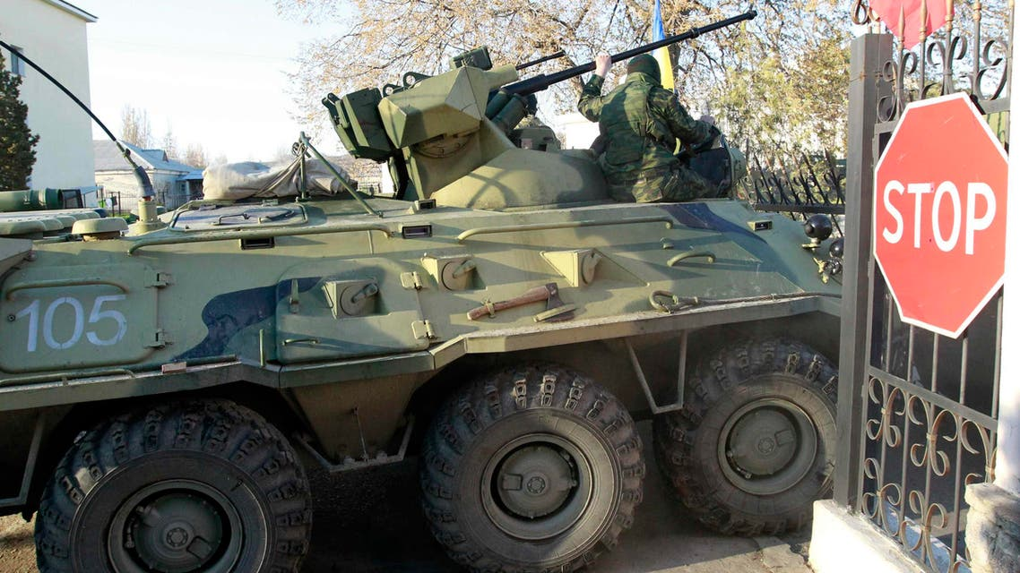 Armed men, believed to be Russian servicemen, drive an armoured vehicle onto the territory of a military airbase as they attempt to take over in the Crimean town of Belbek near Sevastopol March 22, 2014. (Reuters)