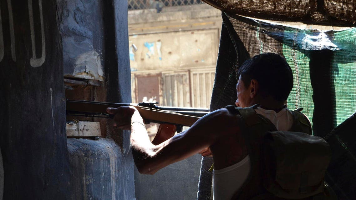 A Sunni Muslim gunman takes his position as he fires his weapon in the Sunni Muslim Bab al-Tebbaneh neighbourhood in Tripoli, northern Lebanon March 21, 2014. (Reuters)