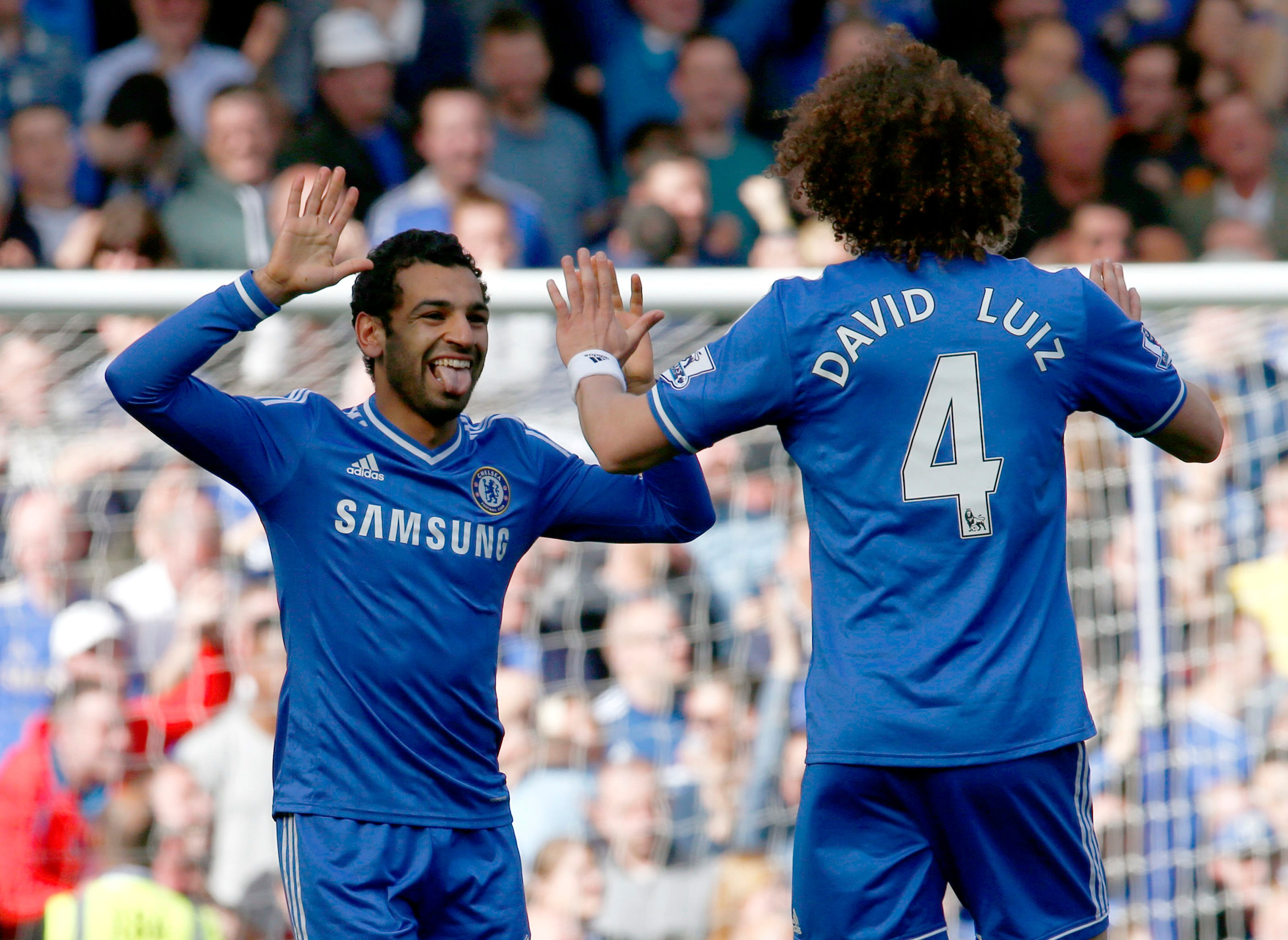 Chelsea's Mohamed Salah (L) celebrates with team mate David Luiz after scoring a goal against Arsenal during their English Premier League soccer match at Stamford Bridge in London, March 22, 2014. (Reuters)