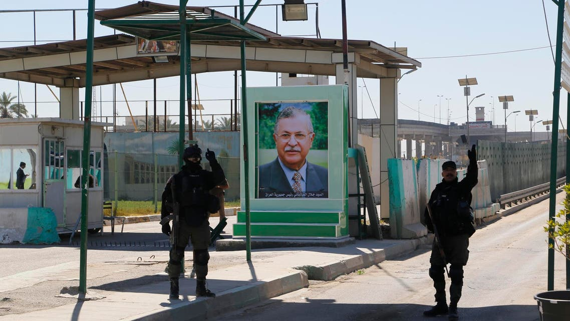 Iraqi SWAT troopers stand guard near a portrait of Iraqi President Jalal Talabani at a checkpoint outside the presidential compound as they replace Kurdish peshmerga guards in Baghdad's Jadriyah district March 23, 2014. (Reuters)