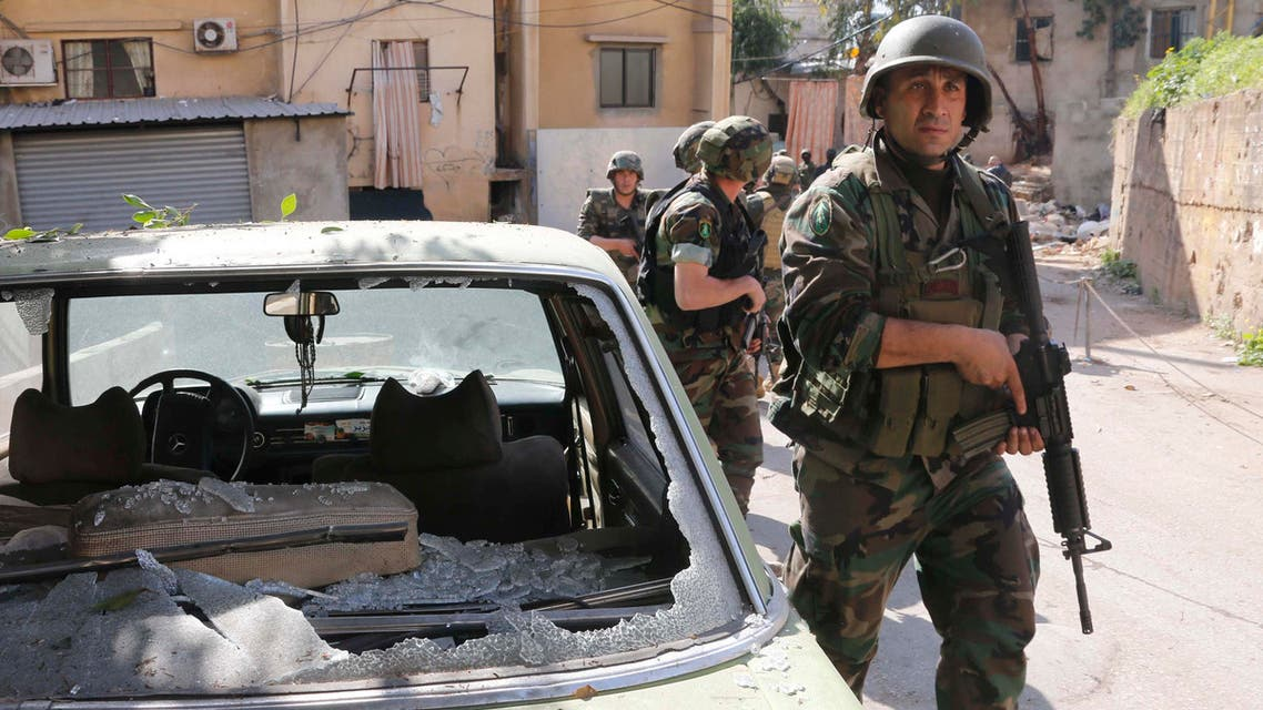 Lebanese Army soldiers walk past a damaged car as they are deployed after clashes in south Beirut March 23, 2014. reuters