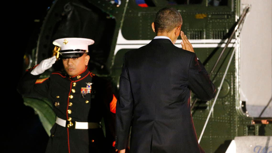 U.S. President Barack Obama (R) salutes as he boards Marine One to begin his travel to Europe from the White House in Washington March 23, 2014 reuters