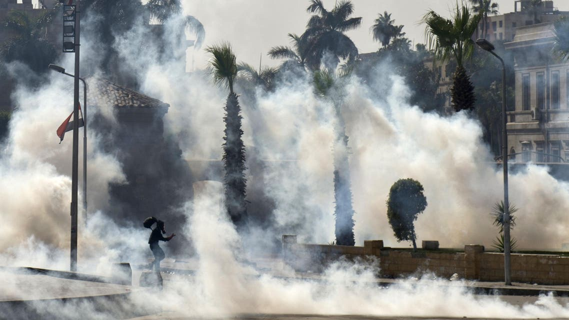An Egyptian Muslim Brotherhood student and supporter of ousted president Mohammad Mursi runs through smoke during clashes with riot police following a demonstration outside Cairo University on March 26, 2014. (Reuters)