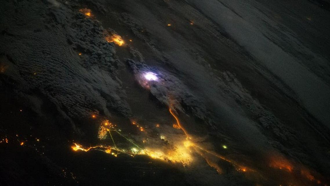 A white flash of lightning is seen over the Gulf, along with the city lights of Saudi Arabia and Kuwait, in this NASA picture taken on Dec 12, 2013. (Photo courtesy: NASA)
