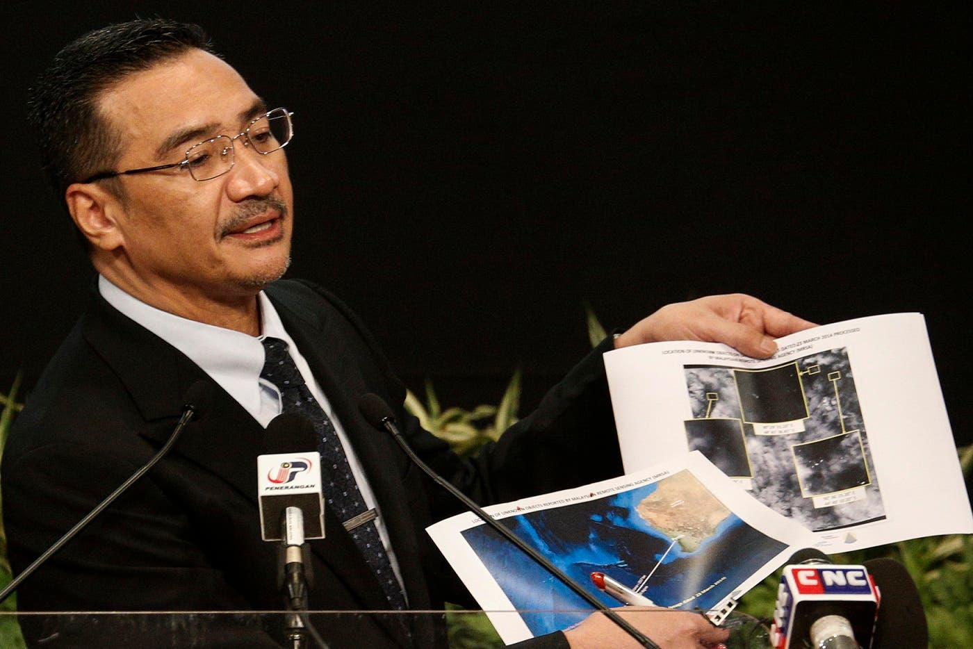 Malaysia's acting Transport Minister Hishammuddin Hussein holds satellite images as he speaks about the search for the missing Malaysia Airlines Flight MH370. (Reuters)
