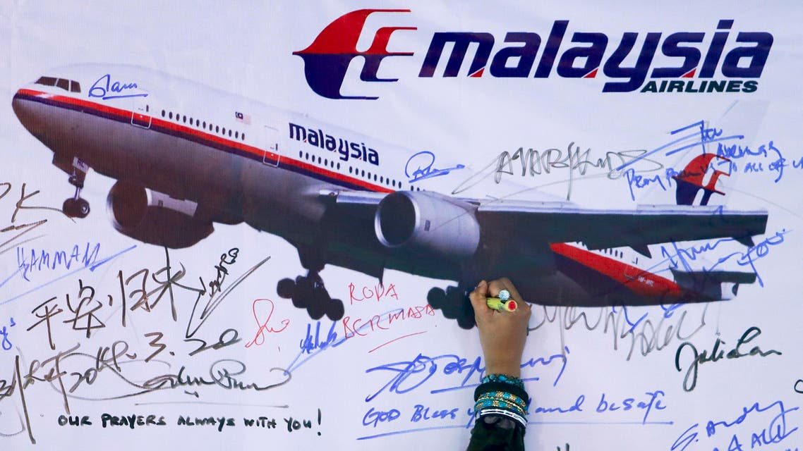 A woman writes a message on a board for passengers onboard missing Malaysia Airlines Flight MH370 and their family members, in Kuala Lumpur on March 22, 2014. (Reuters)
