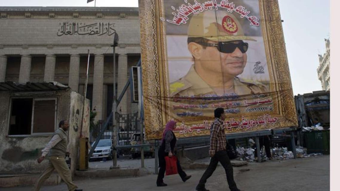 Egyptian walk past a huge poster of Egypt's former Defense Minister and armed forces chief General Abdul Fatah el-Sisi outside the High Court in downtown Cairo, on March 27, 2014. (AFP)