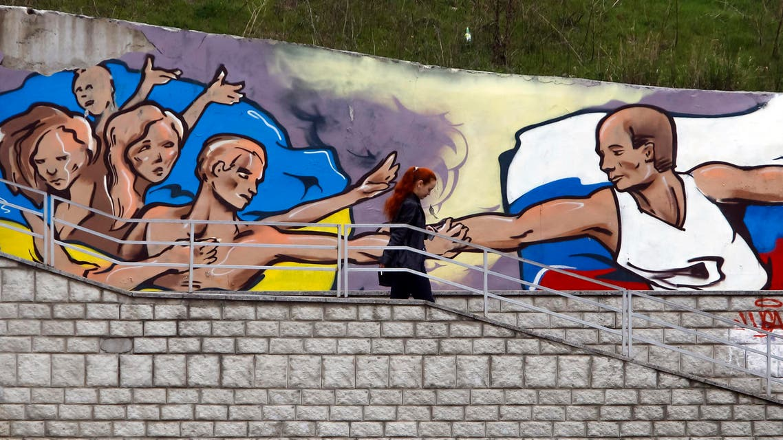 A woman passes a graffiti artwork depicting Russian President Vladimir Putin (R) extending a hand to the Ukrainian people in the Crimean city of Simferopol March 28, 2014.  reuters
