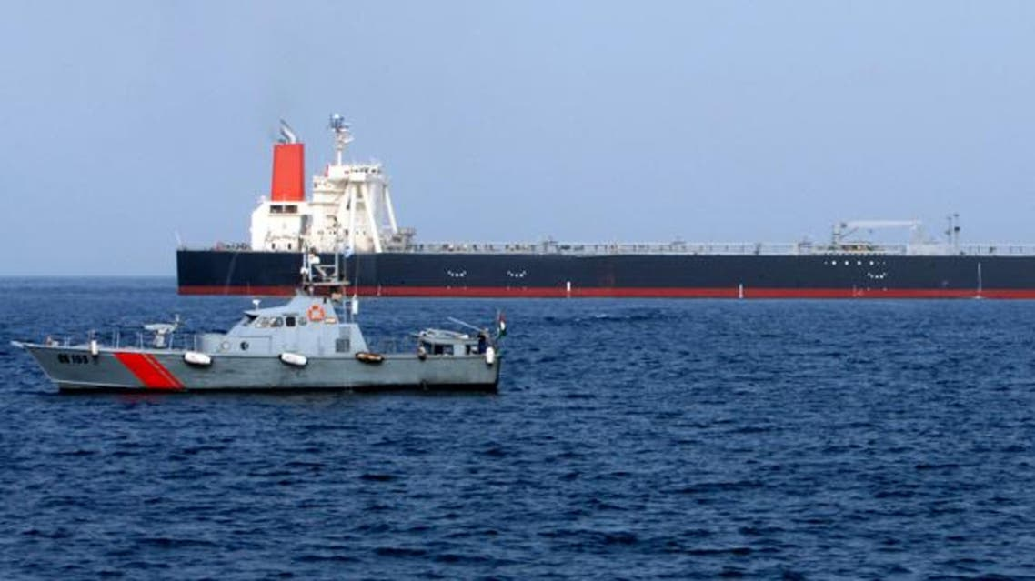 A UAE police boat sails past the M Star oil tanker at sea near Fujairah port in the United Arab Emirates July 29, 2010
