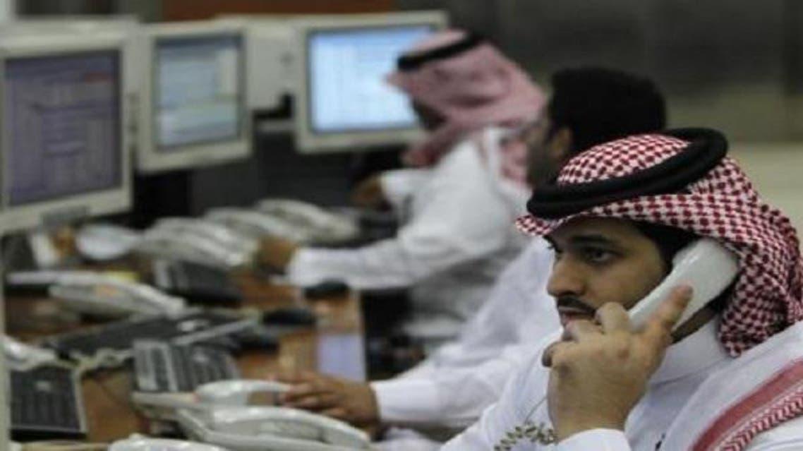 متعاملون يراقبون الأسهم بأحد البنوك في الرياض سوق السعودية