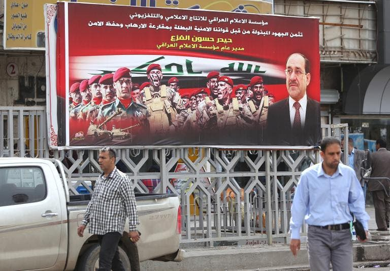 Iraqis walk past an election poster fronted by Iraqi Prime Minister Nuri al-Maliki (R) on March 25, 2014, in Baghdad, ahead of the parliamentary elections in April 2014 (AFP Photo/Ahmad al-Rubaye)