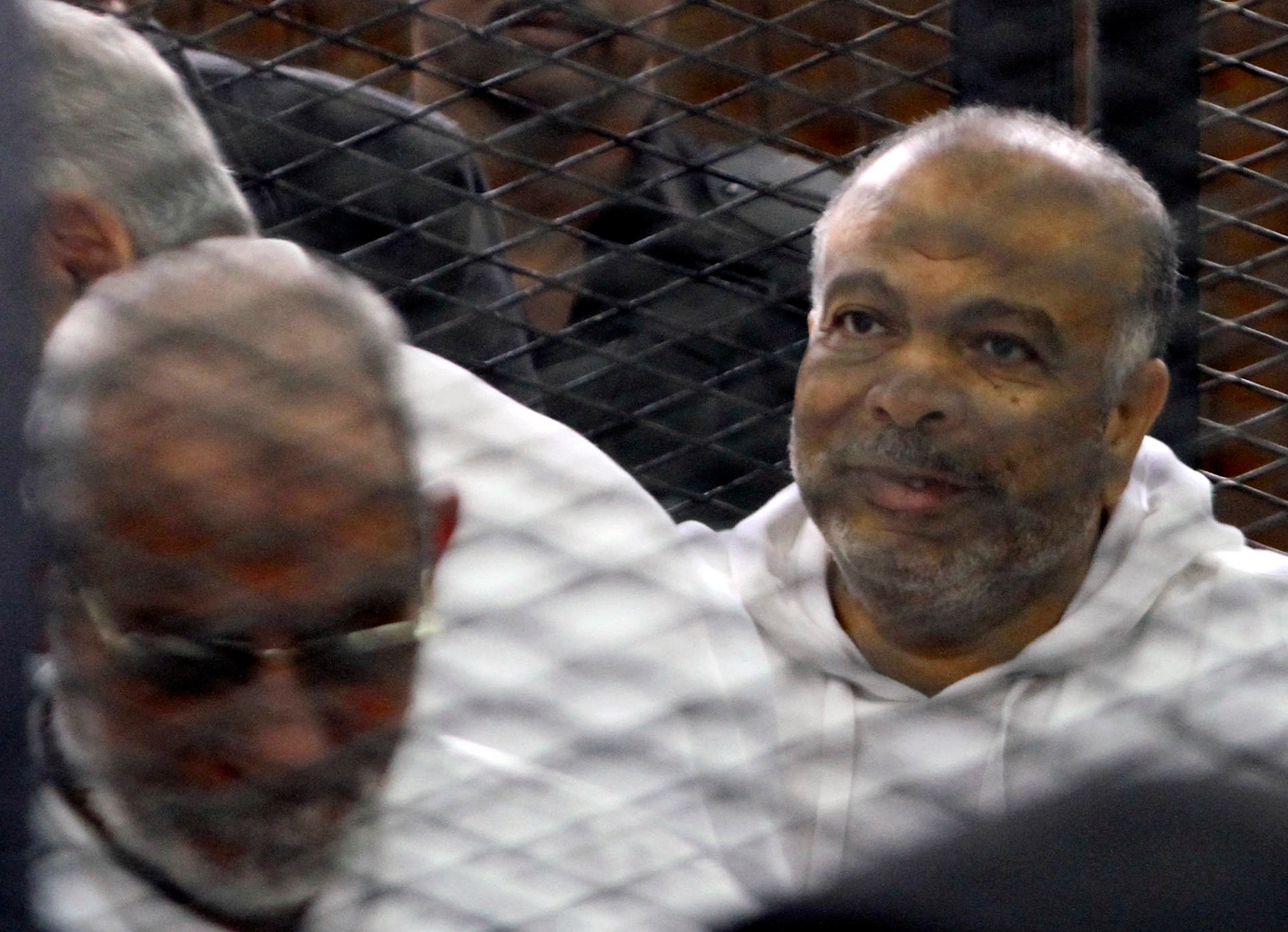 Saad El-Katatni (R), head of the Muslim Brotherhood's Freedom and Justice Party (FJP), sits in the defendant's cage beside the leader of the Muslim Brotherhood Mohammed Badie during their trial with other Brotherhood leaders in a courtroom in Cairo December 11, 2013.