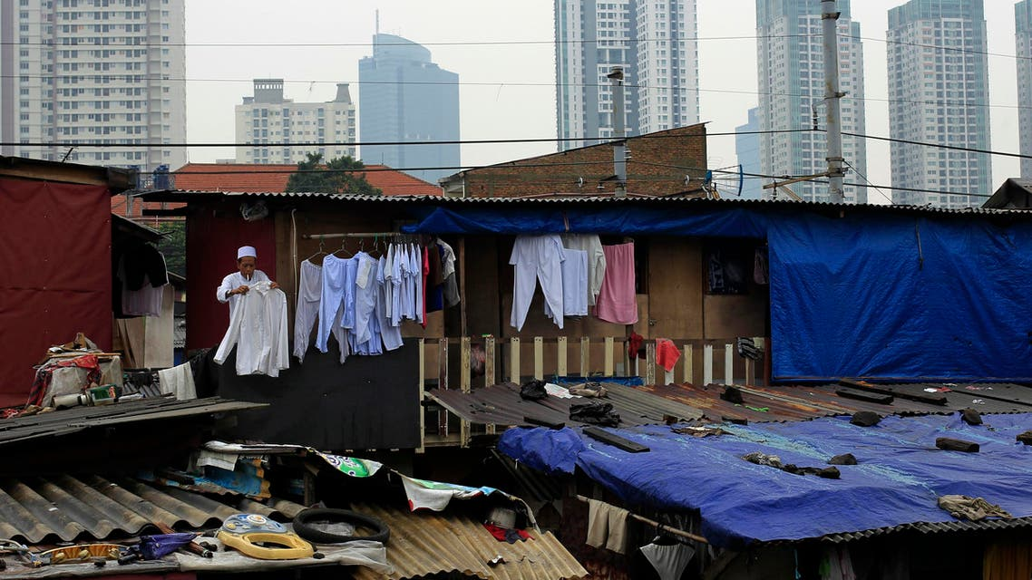 A man with a cigarette in his mouth, hangs out a shirt to dry on the second floor of a house near the business district in Jakarta. (File photo: Reuters)
