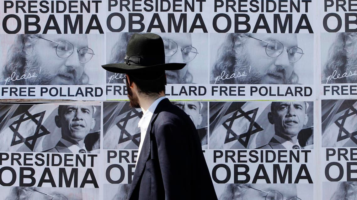 An ultra-Orthodox Jewish man walks past posters calling for U.S. President Barack Obama to free Jonathan Pollard from a U.S. prison. (File photo: AFP)