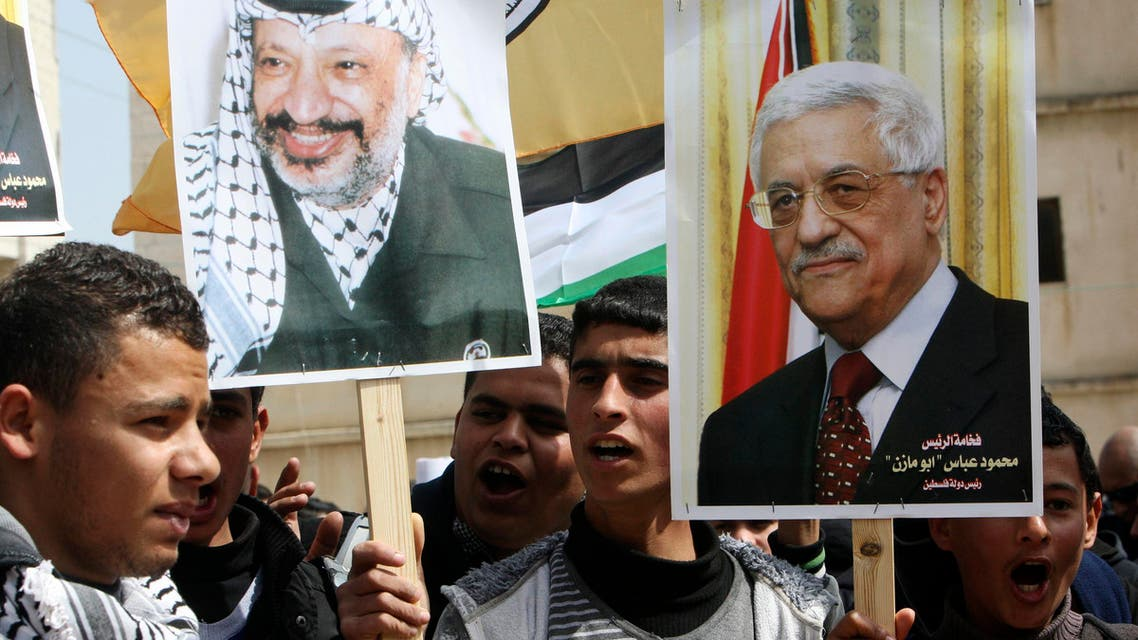 Palestinian Fatah supporters hold placards showing pictures of President Mahmoud Abbas (R) and late leader Yasser Arafat during a rally in support of Abbas in the West Bank village of Tubas near Jenin March 16, 2014. (Reuters)