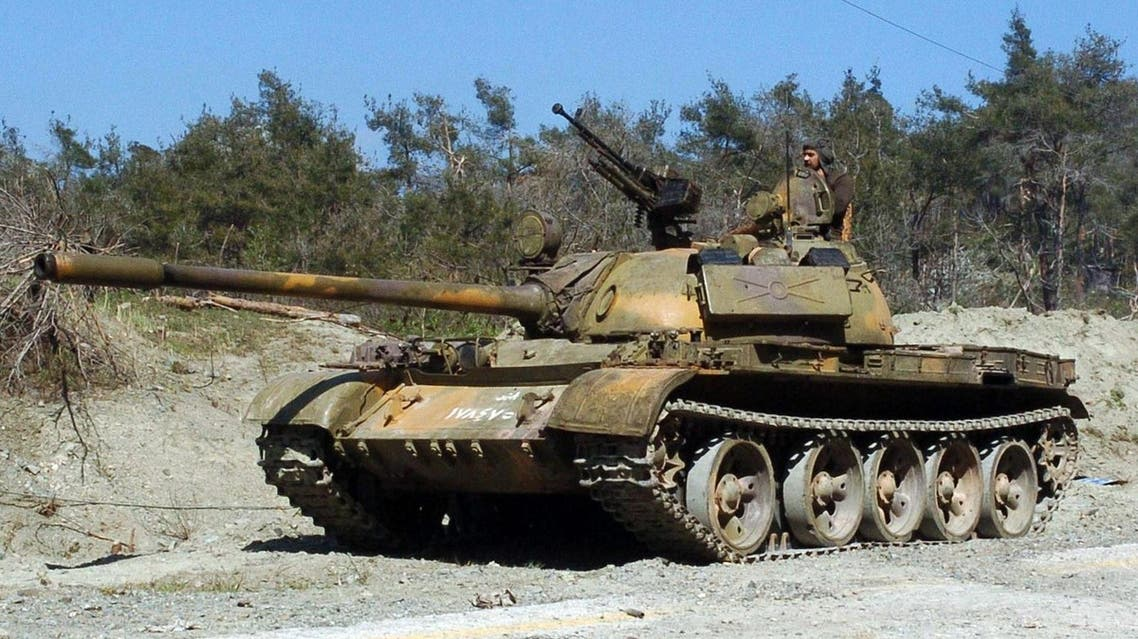 a pro-government fighter standing on a tank at an undisclosed location in the north of Syria's Latakia province. (AFP)