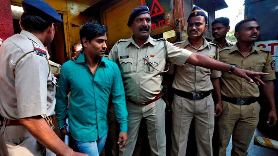 Police escort one of the four men convicted of raping a photojournalist outside a jail in Mumbai March 21, 2014. (Reuters)