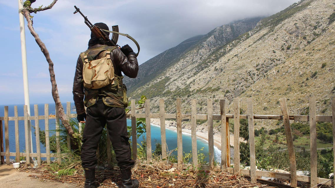 A rebel fighter from the Ansar al-Sham brigade stands on a ridge overlooking the Mediterranean sea reportedly in the village of Kasab, in the northwestern Syrian province of Latakia, on April 4, 2014. AFP