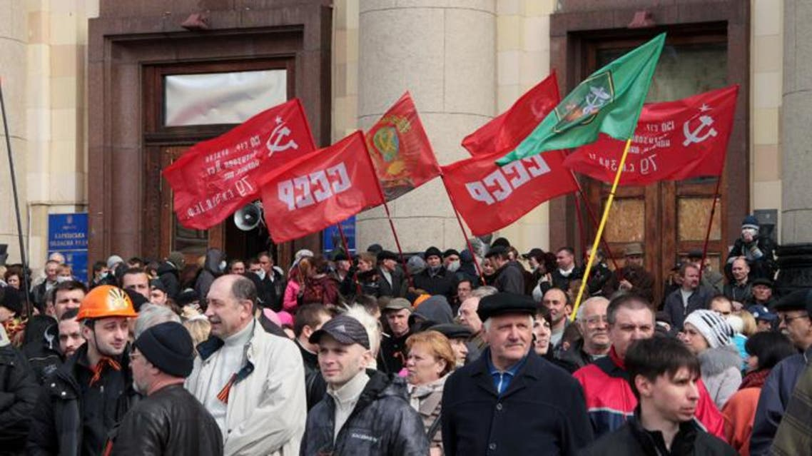 """Pro-Russian activists hold red flags with the communist hammer and sickle and the soviet """"USSR"""" initals during a rally at the regional administration building in the eastern Ukrainian city of Kharkiv on April 7, 2014. (AFP)"""