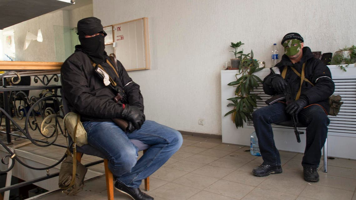 Masked armed men, believed to be pro-Russian protesters, sit inside the offices of the state security service in Luhansk, in eastern Ukraine April 7, 2014. (Reuters)