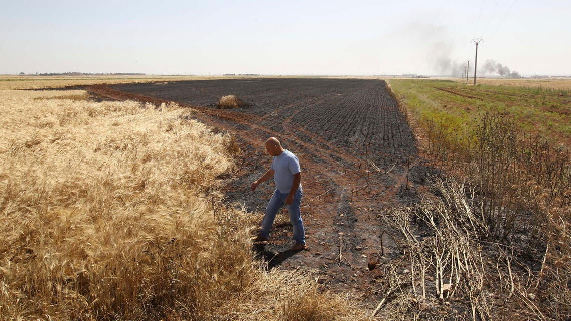 A man inspects an area of a burned wheat field which activists said was caused by shelling by the Syrian regime in Aleppo's countryside June 1, 2013. reuters