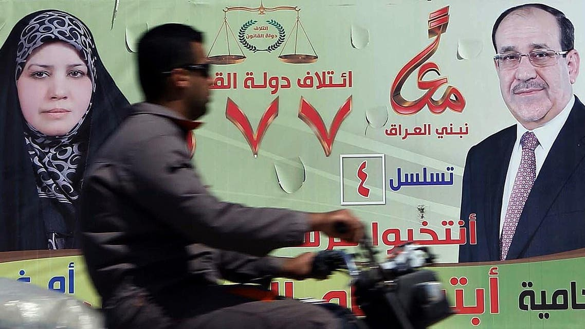A man rides his motor bike past a large election campaign banner showing Iraqi Prime Minister Nuri al-Maliki (R) along a street in the central Shiite Muslim shrine city of Karbala, on April 6, 2014. (AFP)