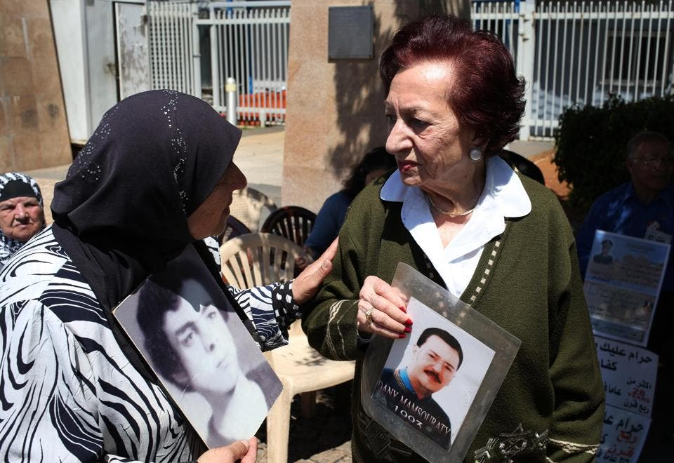 Lebanese Mary Mansourati, 82, right, who her son Dani went missing in Syria in 1992 at the age of 30, holds his portrait as she speaks with Majida Bashasha, 60, who holds a portrait of her brother Ahmad who was kidnapped in 1975 at the age of 18. (AP)