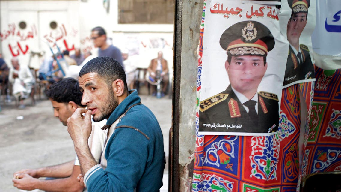 A man sits next to a poster of presidential candidate and former Egyptian army chief Field Marshal Abdel Fattah al-Sisi, in central Cairo, April 8, 2014. (Reuters)