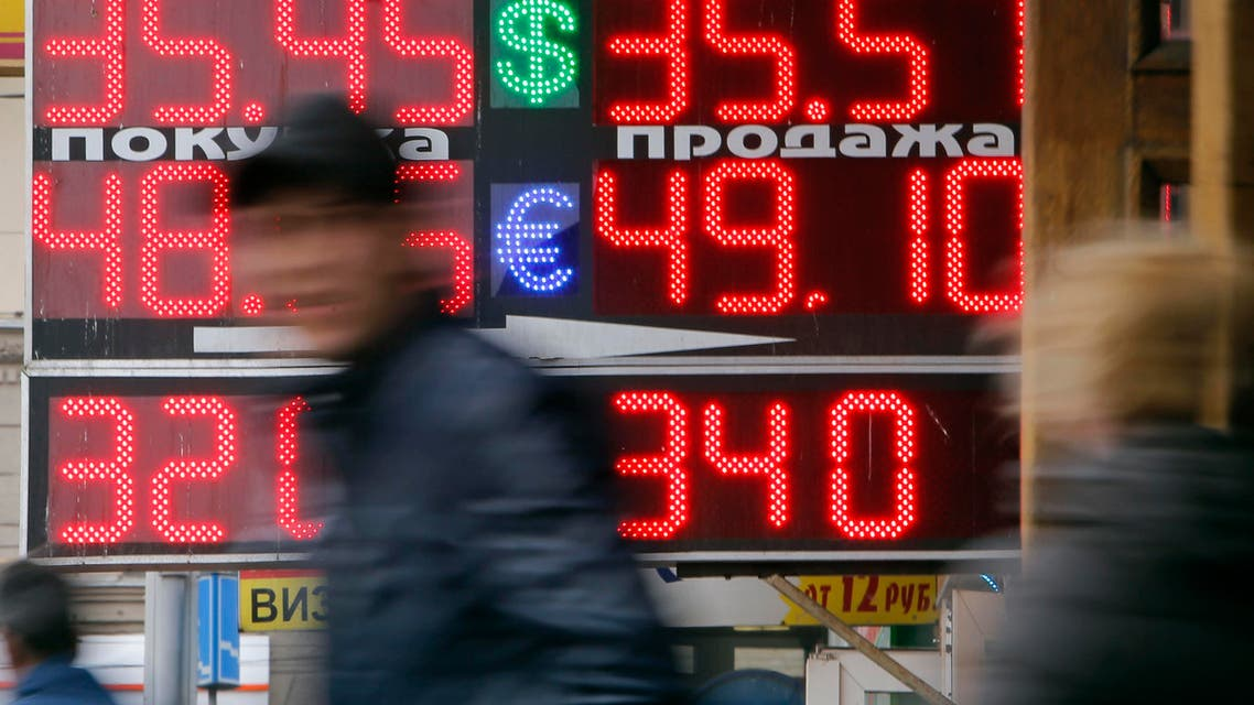 People pass by a board displaying exchange currency rates in Moscow, April 3, 2014. (Reuters)