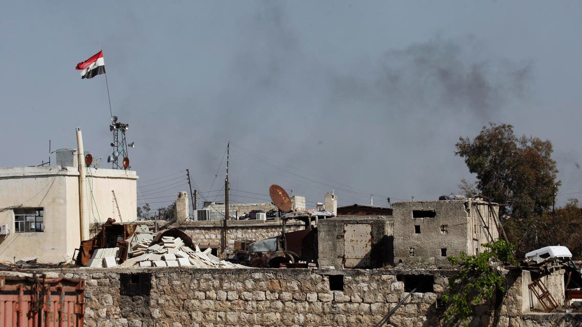 Smoke rises beside a Syrian regime flag in Ramouseh, an area located beside Aleppo Artillery school April 11, 2014. (Reuters)