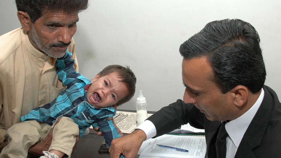 This photograph taken on April 3, 2014 shows a Pakistani lawyer taking the thumb impression from nine-month-old toddler Mohammad Musa on a bail bond in Lahore. (AFP)
