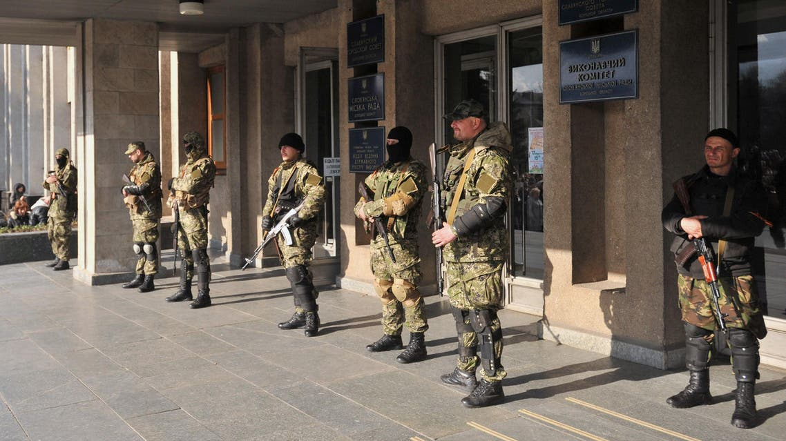 Armed men in military fatigues stand guard outside a regional administration building they seized in the eastern Ukrainian city of Slavyansk on April 14, 2014.  (Reuters)