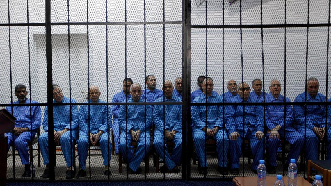 Officials of Muammar Qaddafi's government, including Abdullah al-Senussi (L), ex-spy chief and Buzeid Dorda (2nd L), ex-intelligence chief, sit behind bars during a hearing at a courtroom in Tripoli April 14, 2014.  (Reuters)