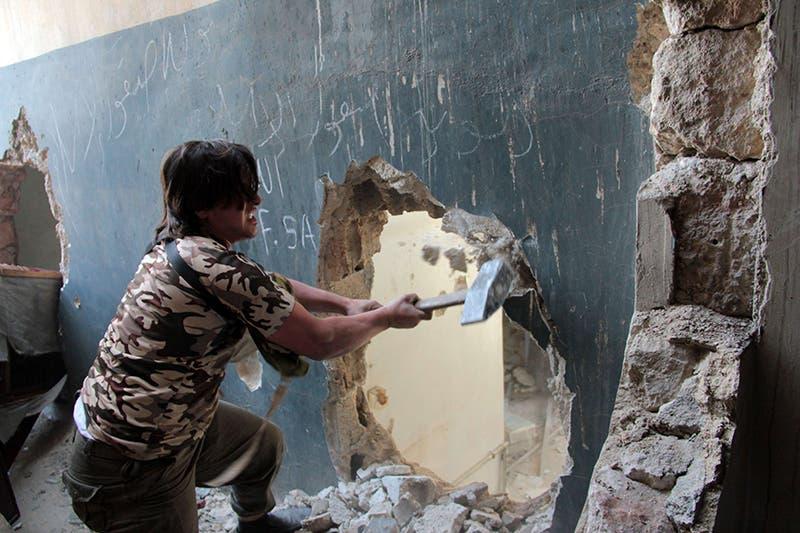 معارض يقوم بعمل فتحة في جدار لتنقل المسلحين اثناء الاشتباكات مع جيش النظام في حلب