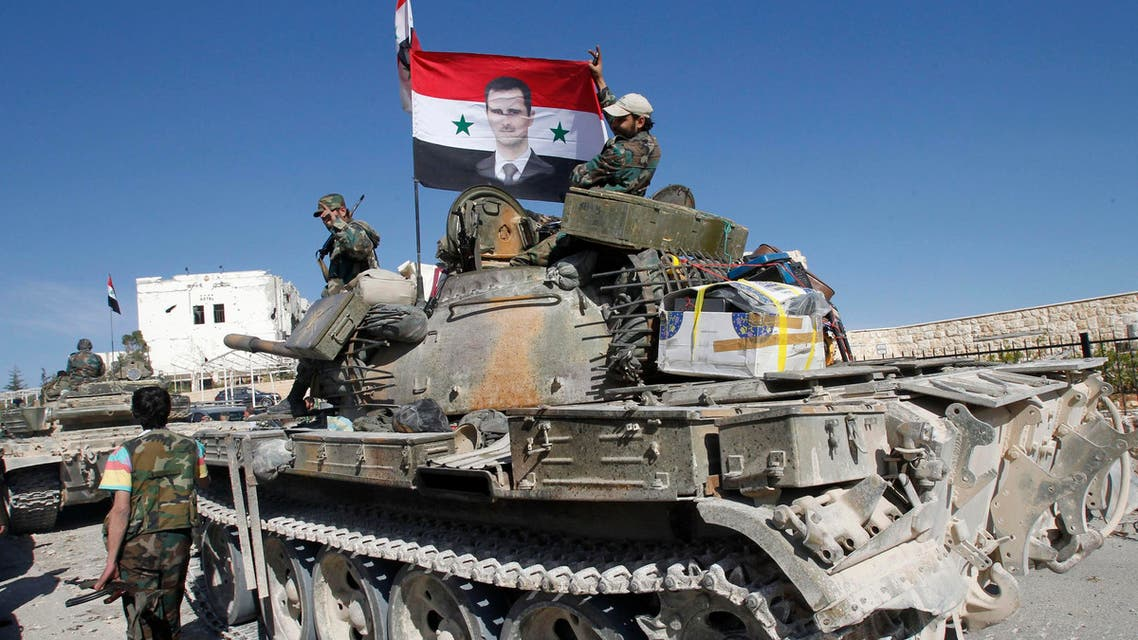 Soldiers loyal to Syria's President Bashar al-Assad hold a Syrian national flag with a picture of Assad, at Maloula village, northeast of Damascus on April 14, 2014. (Reuters)
