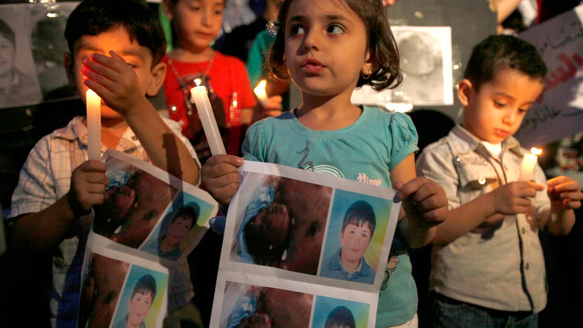 Syrian children carry pictures of 13-year-old Hamza al-Khatib and hold candles during a protest in front of the United Nations building in Beirut June 1, 2011. Reuters