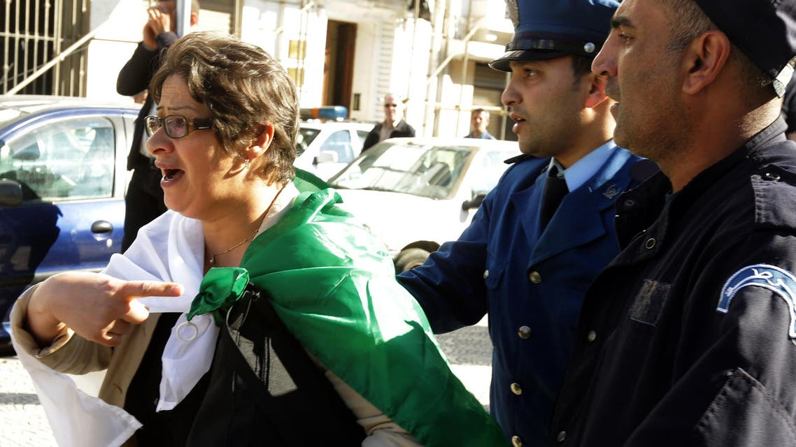 """A member of the Algerian opposition Barakat movement (meaning in Algerian Arabic """"That's enough""""), gestures as she is pushed away by police officers following a protest in Algiers on April 16, 2014. (AFP)"""