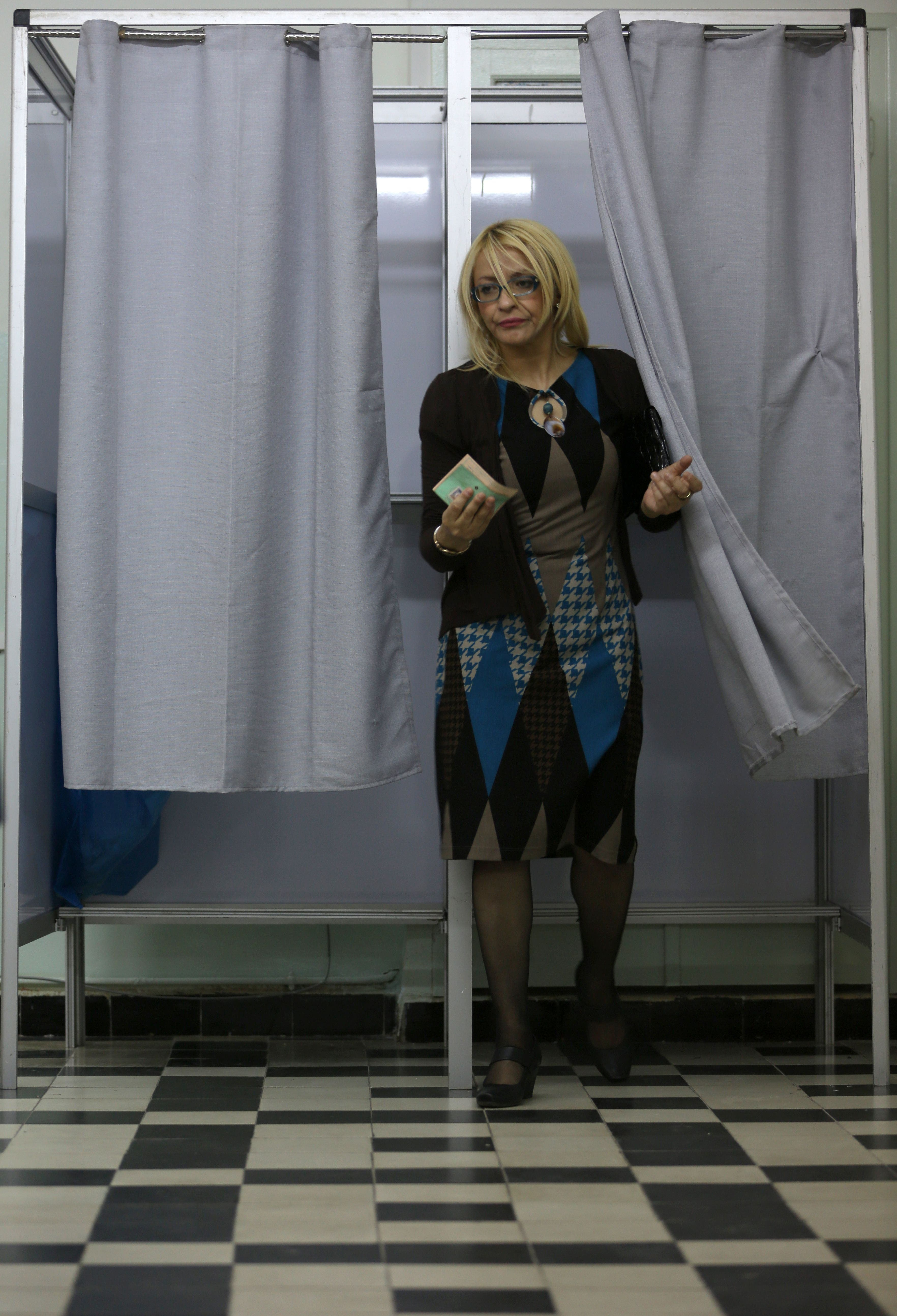 An Algerian woman prepares to cast her vote in the presidential elections at a classroom turned into a polling station on April 17, 2014 in Algiers. (AFP)