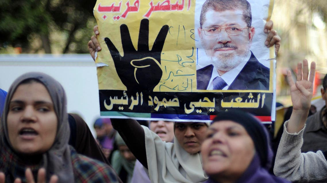"Supporters of Muslim Brotherhood and ousted Egyptian President Mohamed Mursi shout slogans against the military and the interior ministry as they gesture with the sign ""Rabaa"", or ""Four"", during a protest around Ain Shams square in east Cairo February 14, 2014. reuters"