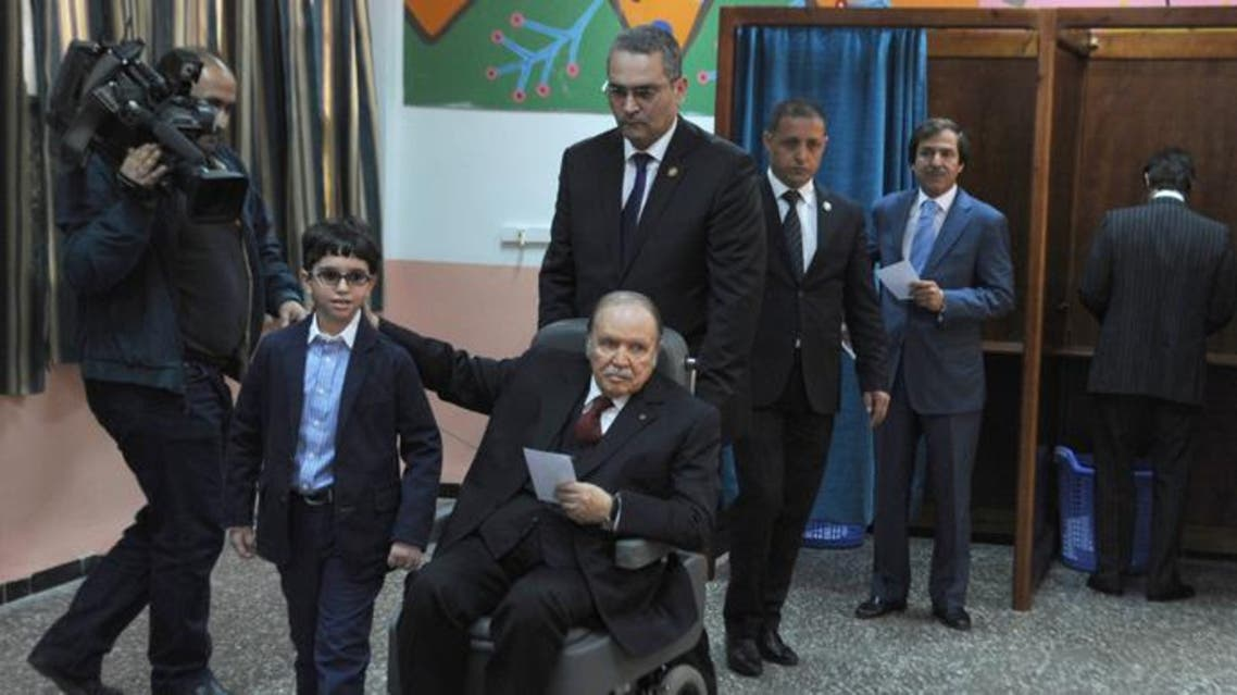 Algeria's ailing President Abdelaziz Bouteflika (C), running for re-election, is pushed in a wheelchair next to his nephew after casting his ballot at a polling station in Algiers on April 17, 2014.