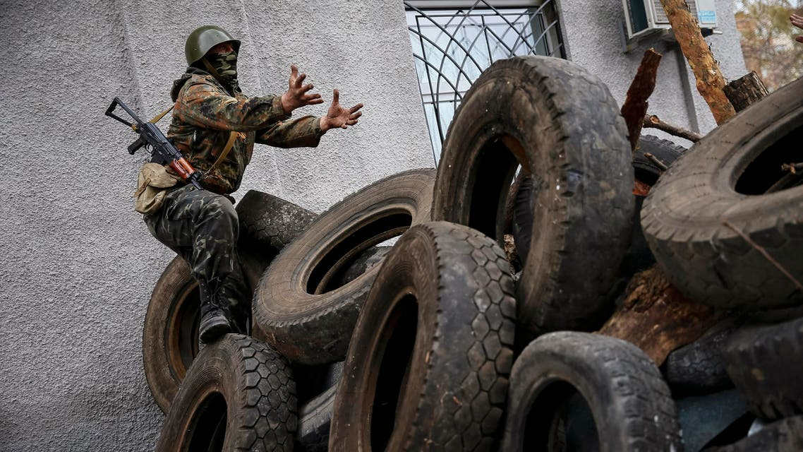 An armed man gestures from a barricade in front of the police headquarters in Slaviansk April 12, 2014. reuters