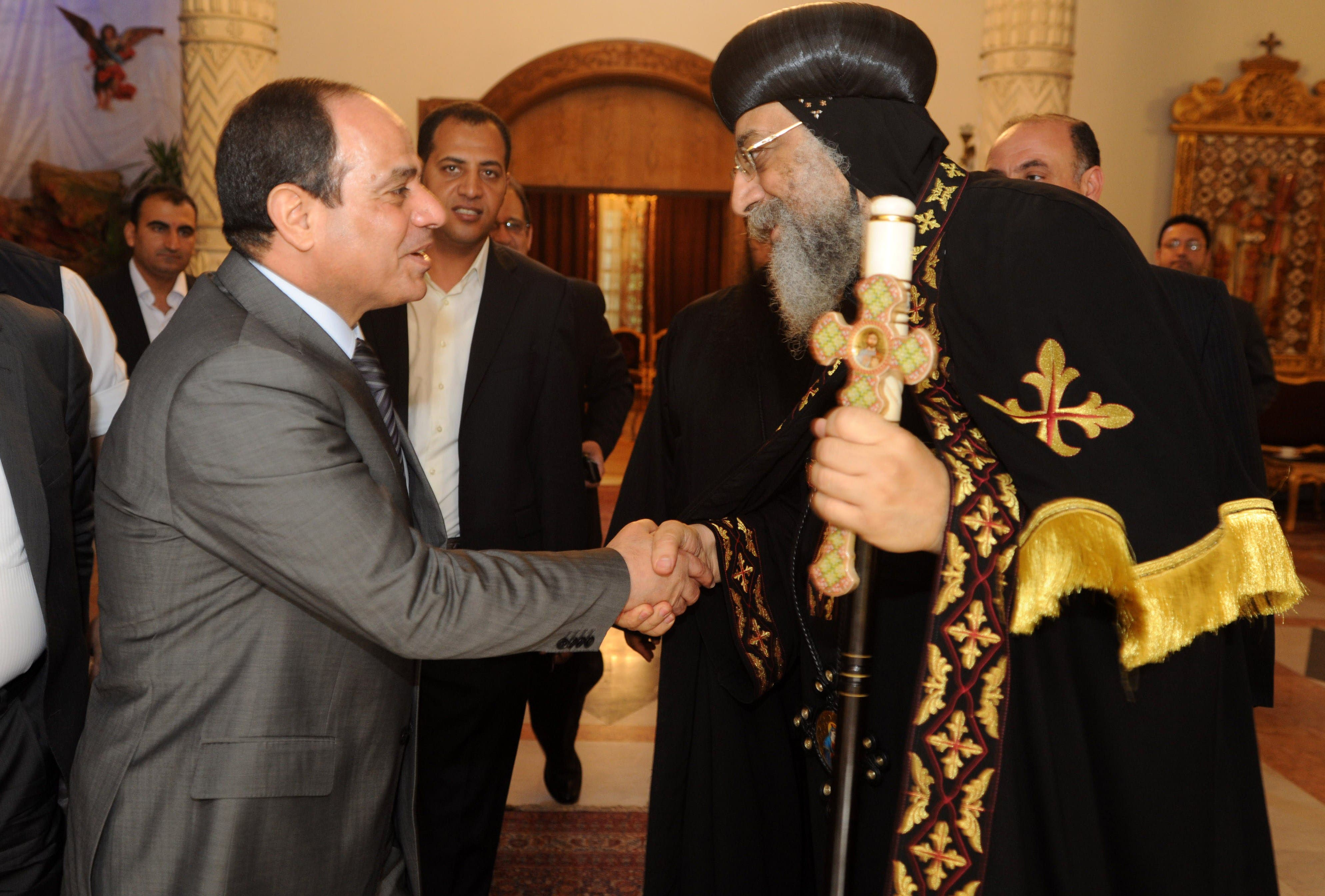 A handout picture released by the press office of Abbasiya Cathedral shows Egyptian former Defence Minister and armed forces chief General Abdul Fatah al-Sisi (L) shaking hands with Pope Tawadros II, pope of Egypt's Coptic Orthodox Church on April 19, 2014 during a visit at Cathedral of Abbasiya in Cairo. (AFP)