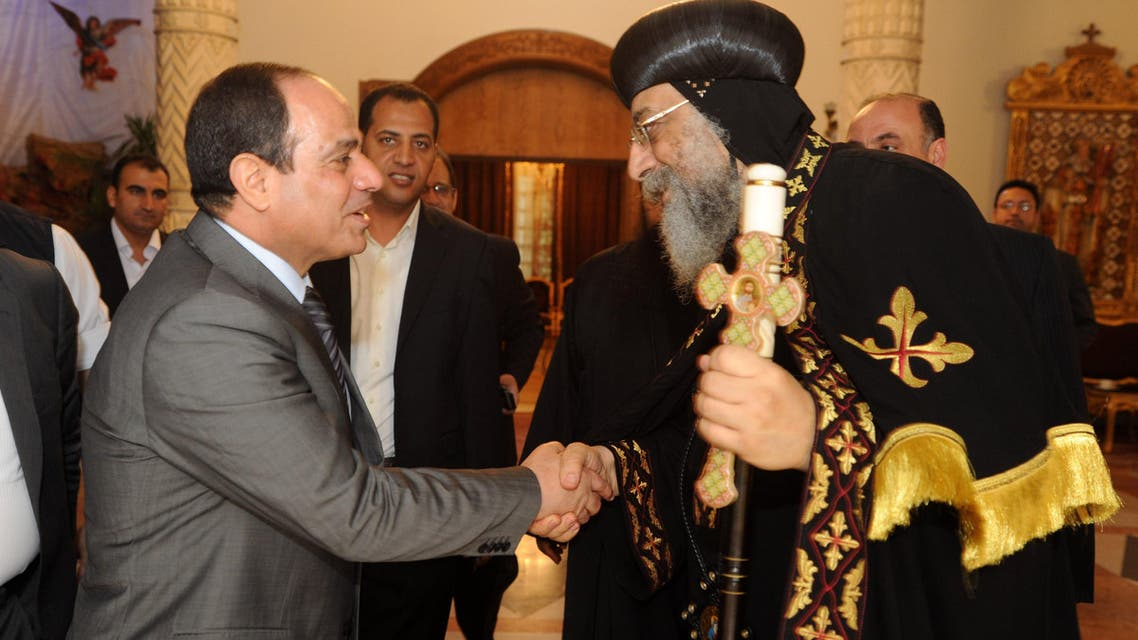A handout picture released by the press office of Abbasiya Cathedral shows Egyptian former Defence Minister and armed forces chief General Abdul Fatah al-Sisi (L) shaking hands with Pope Tawadros II, pope of Egypt's Coptic Orthodox Church on April 19, 2014 during a visit at Cathedral of Abbasiya in Cairo. AFP