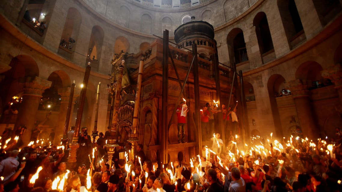 Christian Orthodox worshippers hold up candles lit from the 'Holy Fire' as thousands gather in the Church of the Holy Sepulchre in Jerusalem's old city on April 19, 2014 during the 'Holy Fire' ceremony on the eve of the Orthodox Easter. AFP