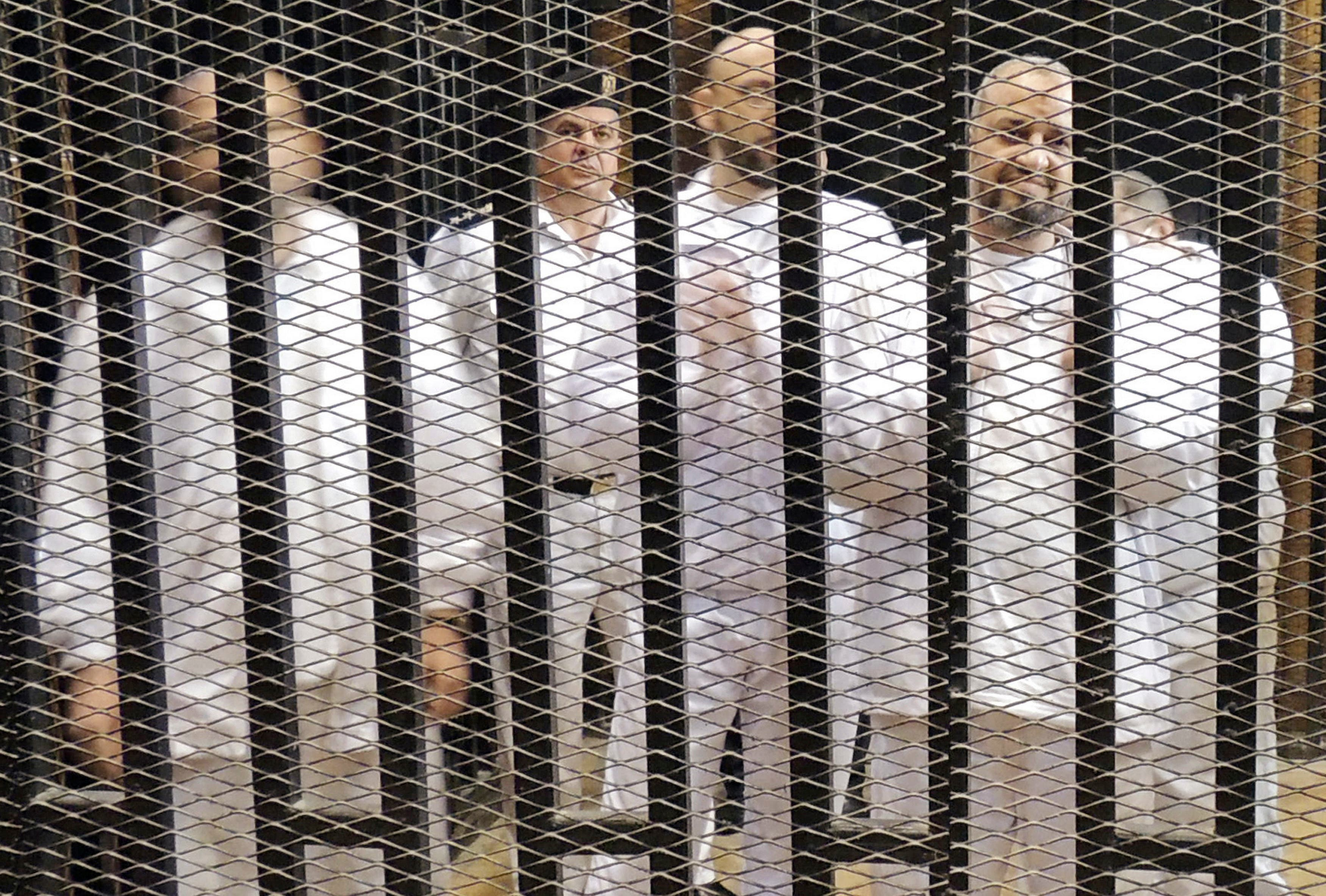 Muslim Brotherhood leader Mohamed El-Beltagy (R) stands with other senior figures in a cage in a courthouse on the first day of their trial in Cairo November 4, 2013. reuters